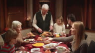 Granddaughter waiting for grandpa to give her slice of turkey at Thanksgiving dinner video
