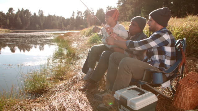 Grandfather and father sit teaching boy to fish by a lake video