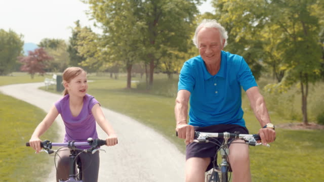 TS Grandfather and granddaughter cycling through the park video
