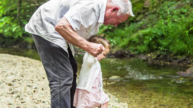 Grandfather and Granddaughter playing next to the river video