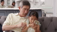 Grandfather And Granddaughter Using Mobile Phone Shot On R3D video