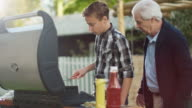 Grandfather and Grandon Are Cooking Burgers on Grill at Bright Summer Day. video