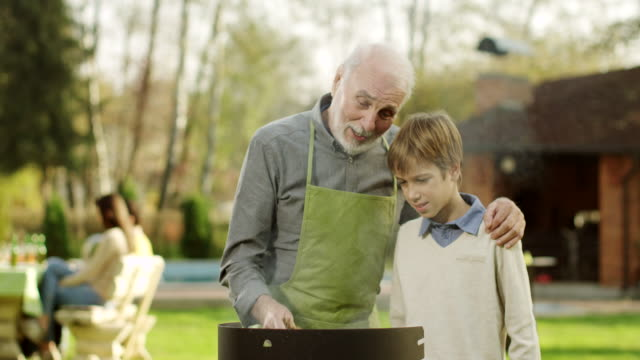 Grandfather and Grandson Having a Barbecue video