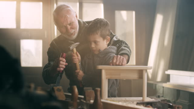 Grandfather and grandson in workshop video