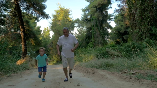 Grandfather and grandson jogging in the forest video