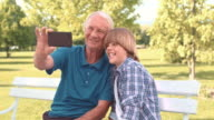 Grandfather and grandson making a selfie on park bench video