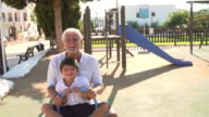 Grandfather And Grandson On Seesaw In Playground video