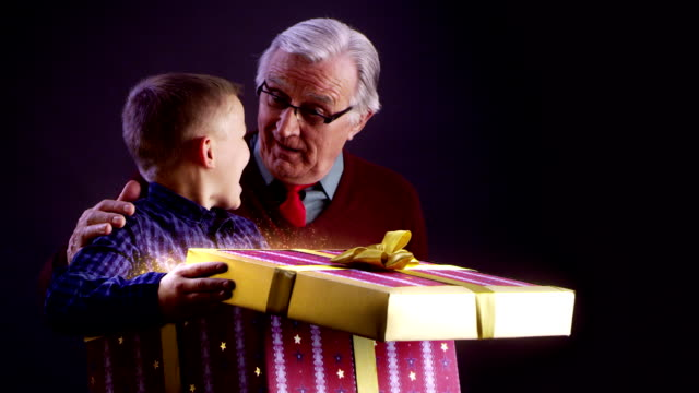 Grandfather and grandson opening Christmas gift video