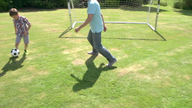 Grandfather And Grandson Playing Football In Garden At Home video