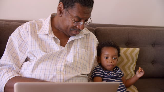 Grandfather And Grandson Sit On Sofa At Home Using Laptop video