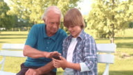 Grandfather and grandson using a phone while sitting in park video