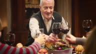Grandfather clinking glasses with his family at Thanksgiving table video