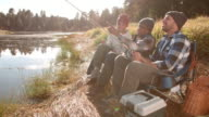 Grandfather, father and son sit fishing by a rural lake video