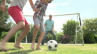 Grandfather, Grandson And Father Playing Football In Garden video