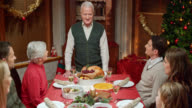 Grandfather making a speech at Christmas table and family applauding video