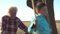 Grandfather pushes happy grandson on swing video
