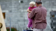 Grandfather puts his grandchild on a swing video