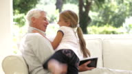 Grandfather Reading Book On Sofa When Granddaughter Gives Him Cuddle video