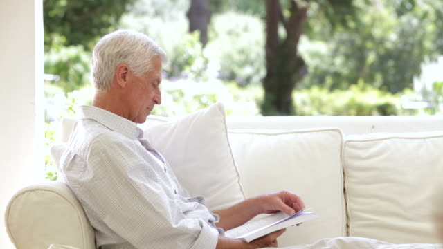 Grandfather Reading On Sofa When Grandchildren Give Him A Cuddle video