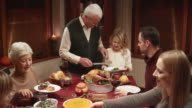 Grandfather serving turkey slices onto granddaughters plate video
