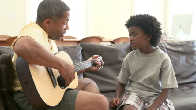 Grandfather Teaching Grandson To Play Guitar video