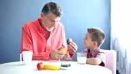 Grandfather teaching little boy to eat healthy food video