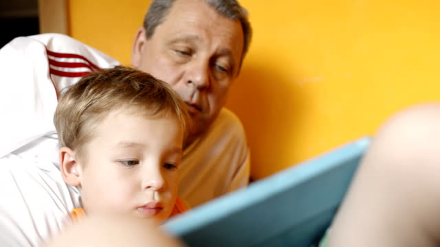 Grandfather watching grandson playing on pad video