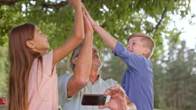 SLO MO Grandkids doing a high five with their granddad at a picnic video
