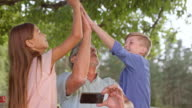SLO MO Grandkids doing high five with granddad at picnic video