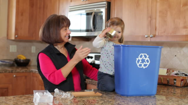 Grandma and Grandchild in kitchen recycling video