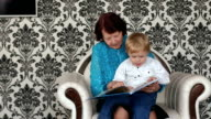 Grandma and little boy sitting on sofa with book. video
