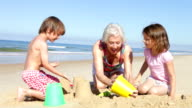 Grandmother And Grandchildren Making Sandcastles On Beach video