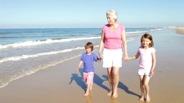Grandmother And Grandchildren Walking Along Beach video