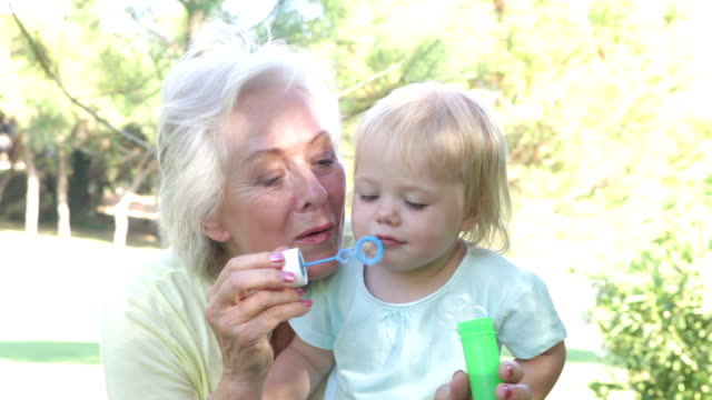 Grandmother And Granddaughter Blowing Bubbles Outdoors video
