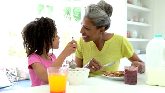 Grandmother And Granddaughter Having Breakfast Together video