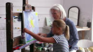 Grandmother And Granddaughter Painting In Studio Shot On R3D video
