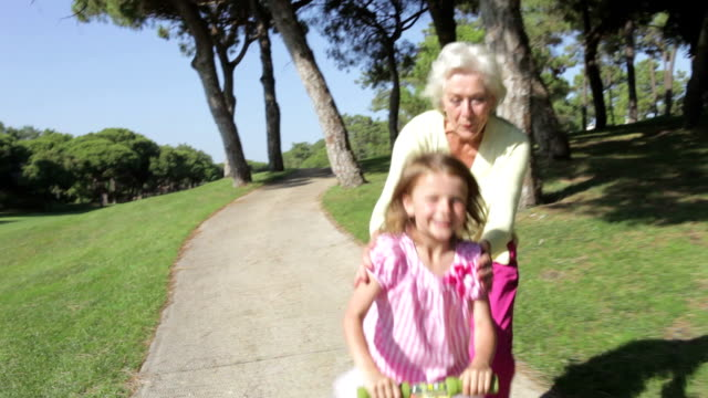 Grandmother And Granddaughter Riding Scooter In Park video