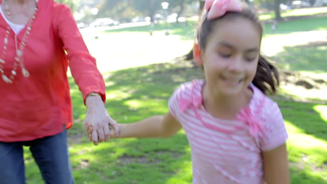 Grandmother And Granddaughter Running Through Park Together video