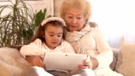 Grandmother and granddaughter using Tablet PC video