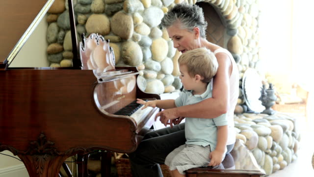 Grandmother and grandson playing piano video