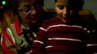 grandmother and grandson sitting in a chair talking video