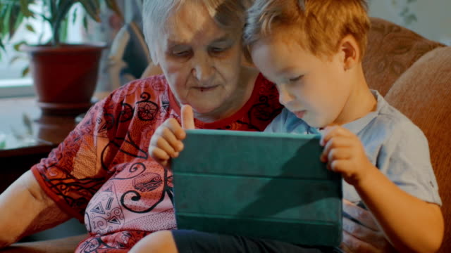 Grandmother and grandson use tablet at home video