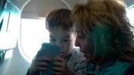Grandmother and grandson with cell in the plane video