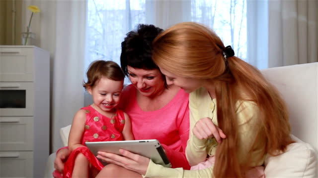 Grandmother and mother fun teaching little girl to use the touchpad. video