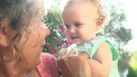 Grandmother At Home Playing With Granddaughter In Garden video