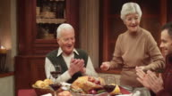 Grandmother bringing the Thanksgiving turkey to the table video