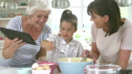 Grandmother, Granddaughter And Mother Baking Cake In Kitchen video