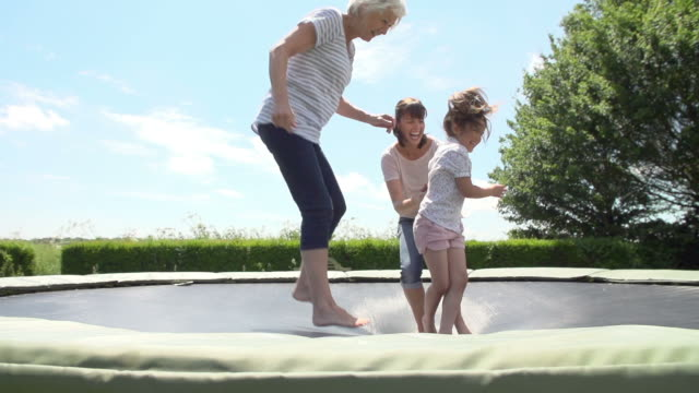 Grandmother, Granddaughter And Mother Bouncing On Trampoline video