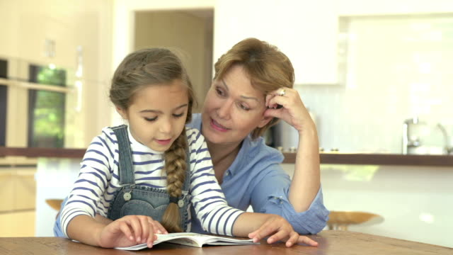 Grandmother Helping Granddaughter With Reading At Home video