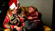 grandmother in New Year's cap hugs her grandson on a background of the Christmas tree video